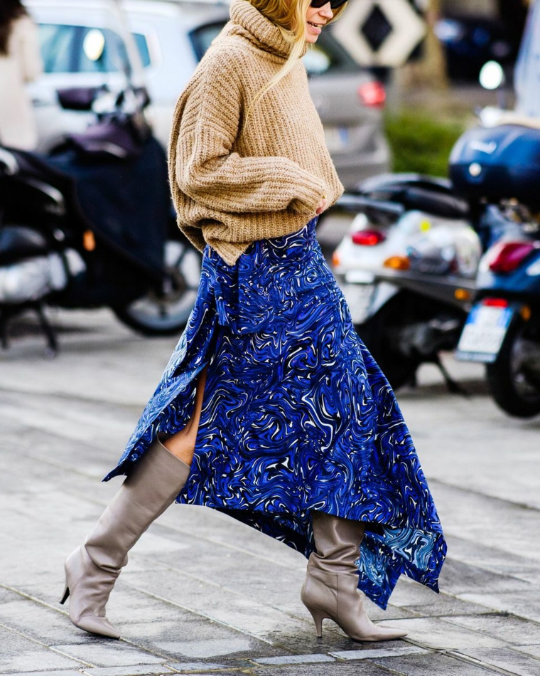 Stivali con tacco grigio, gonna larga con blu, maglione di lana cappuccino, donna che cammina