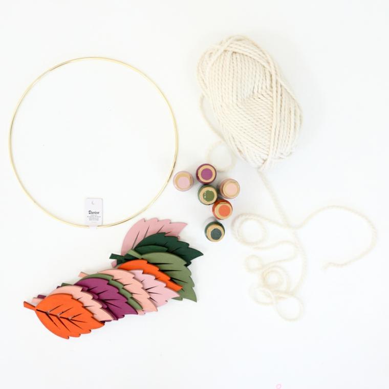 Foglie di legno colorate, anello di metallo, rotolo di lana bianca, composizioni autunnali