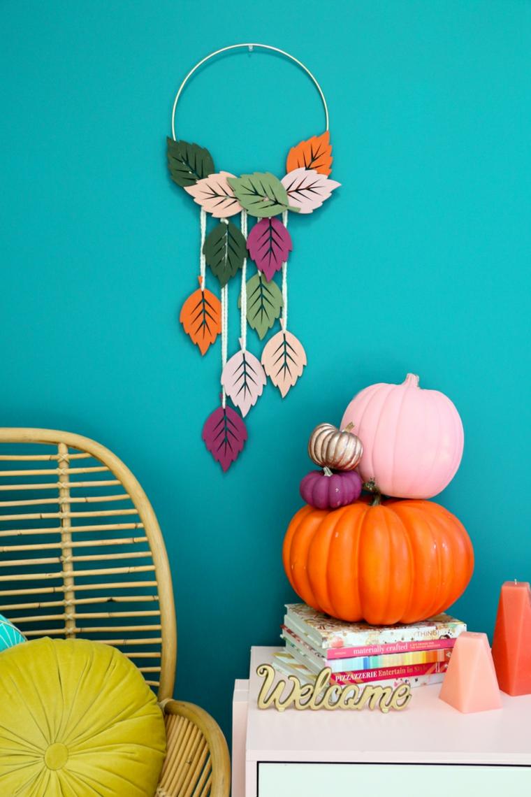 Zucche e libri, anello e foglie, addobbi autunnali, sedia di rattan con cuscini, parete dipinta di blu