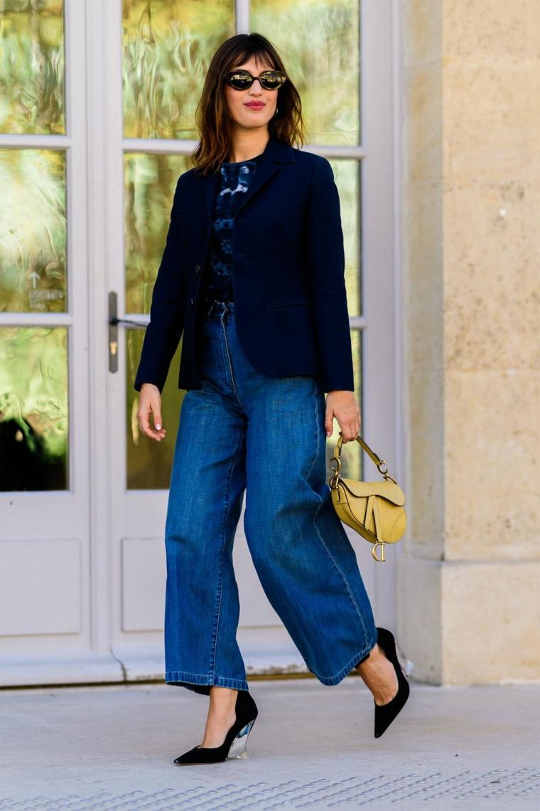 Donna che cammina, jeans a zampa larga, giacca di colore nero, capelli long bob con frangia