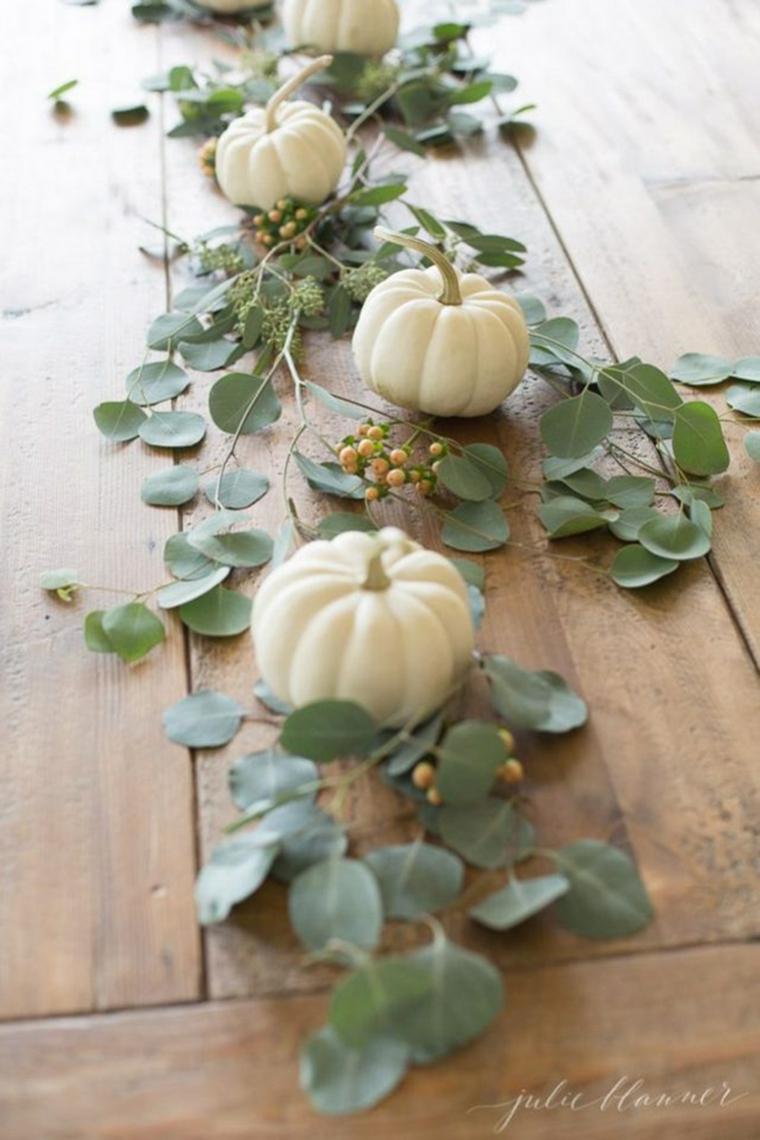 Tavola con zucche, rametti con foglie verdi, addobbi autunno, mini zucche bianche