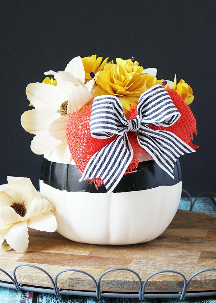 Centrotavola con zucca, zucca intagliata con fiori, tavola con vaso di fiori