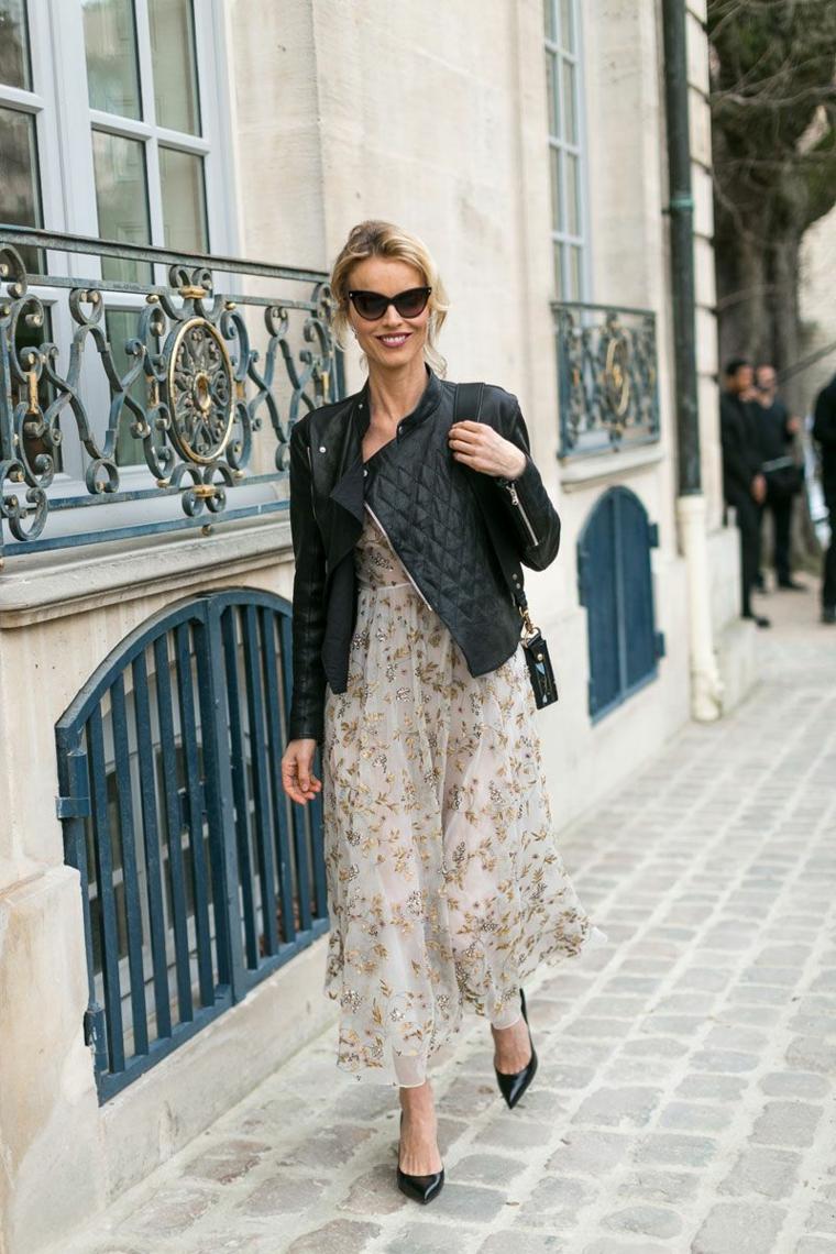 Donna che cammina, ragazza bionda sorridente, giacca in pelle nera, maxi abito floreale