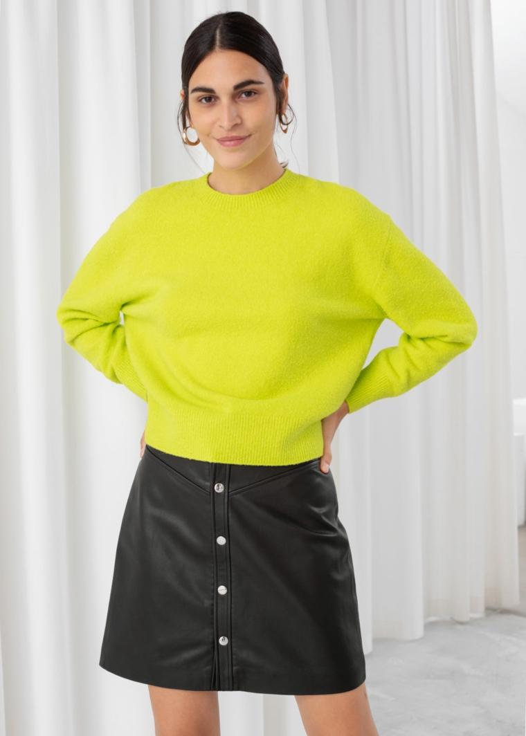 Maglione di lana colore neon, gonna corta in pelle, donna con capelli legati