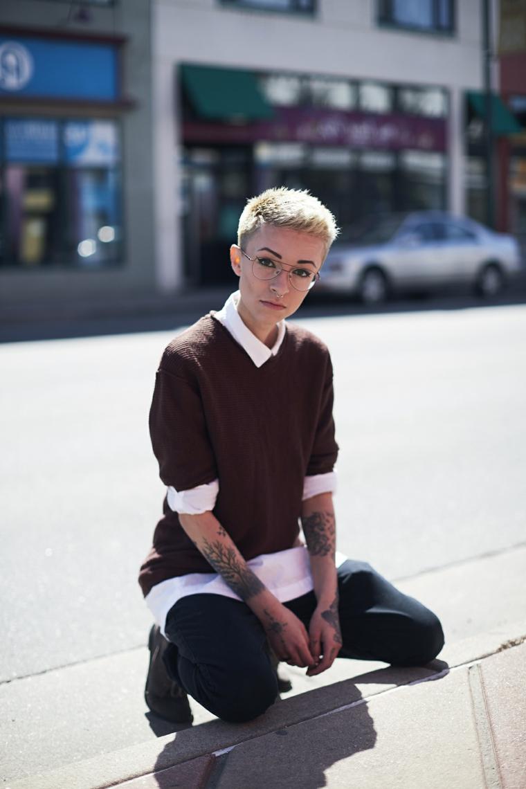 Donna con tatuaggio sulle braccia, capelli biondi cortissimi, tendenze autunno inverno 2019