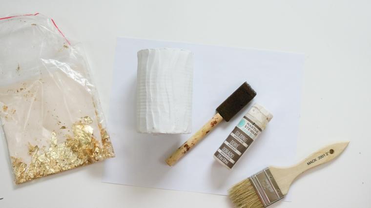 Materiali per fare un vaso, pennello con spugna, sacchettini con foglietti, barattolo di latta, decori natalizi