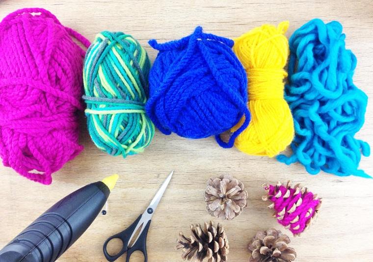 Pigne con filo di lana, rotoli di lana, pistola per colla a caldo, lavoretti di Natale facili