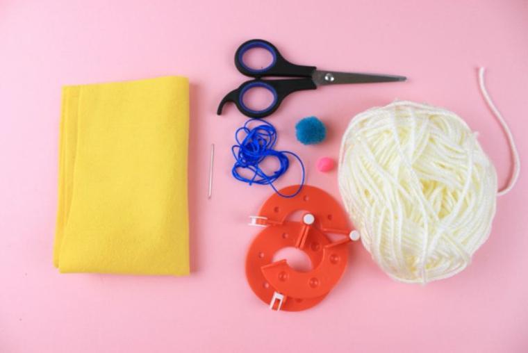 Materiali per fare uno gnomo, rotolo di lana, feltro di colore giallo, filo blu e ago