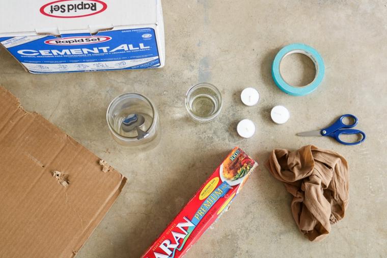 Materiali per fare un portacandela, tre piccole candele, scatola con calcestruzzo