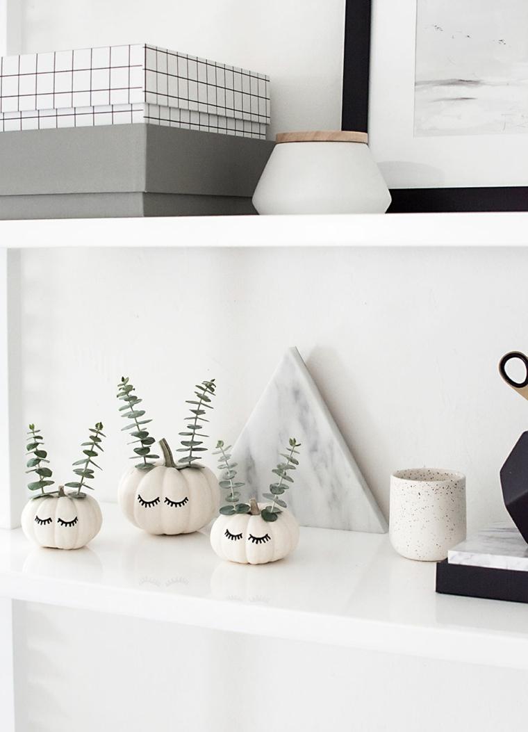 Zucche finte dipinte di bianco, mensola con decorazioni, addobbi per Halloween