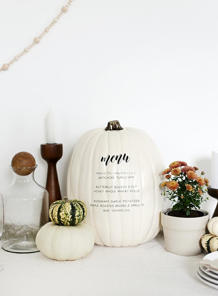 Menu scritto su una zucca, decorazioni semplici per Halloween, zucche dipinte di bianco