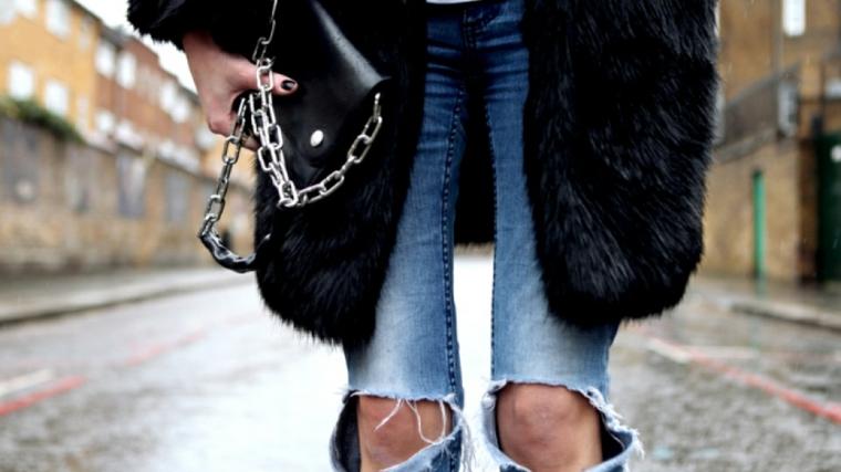 Moda abiti inverno, jeans chiari con strappi, cappotto pelliccia nero, borsa tracolla con catena