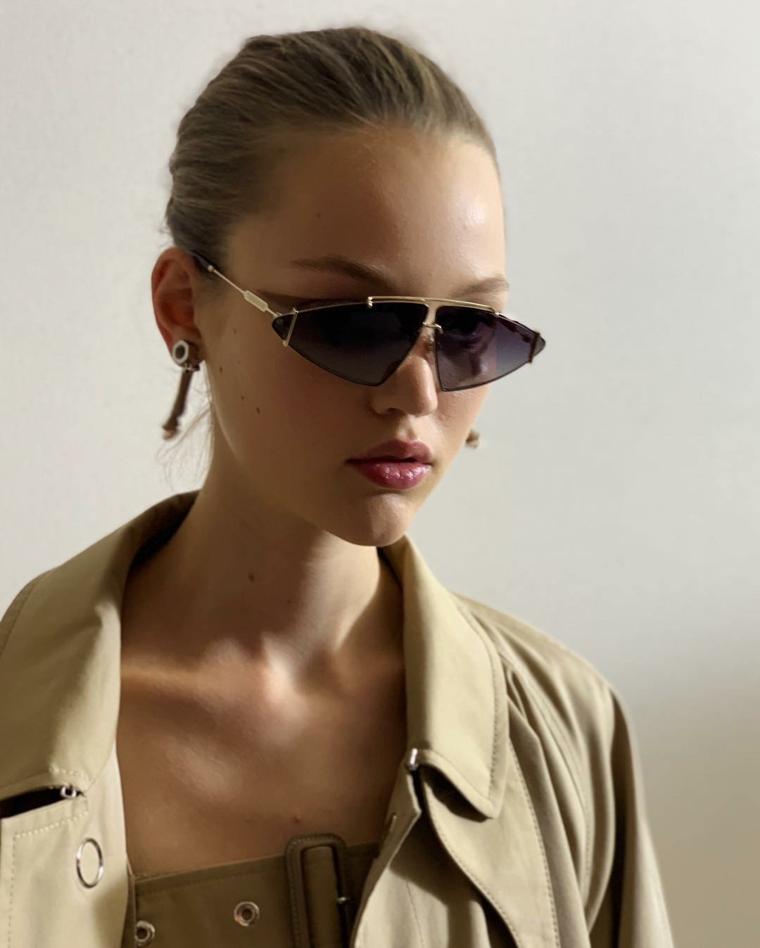 Cappotto tench colore grigio, occhiali da sole forma triangolare, donna con capelli legati