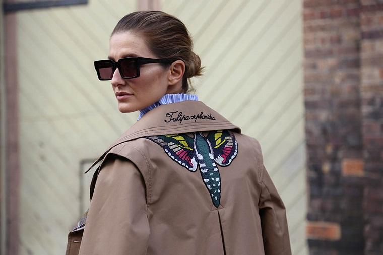 Tendenze autunno inverno 2019, donna con occhiali da sole, giacca con scritta, capelli raccolti a chignon