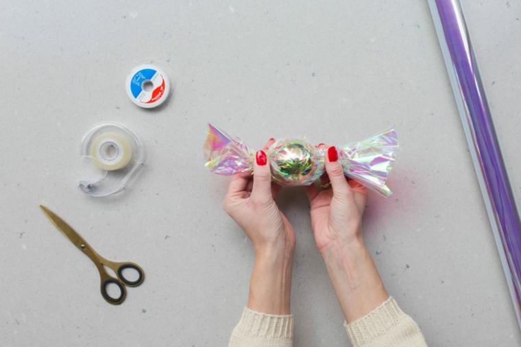 Palline di Natale fai da te, nastro adesivo e forbici, pallina a forma di caramella in cellophane