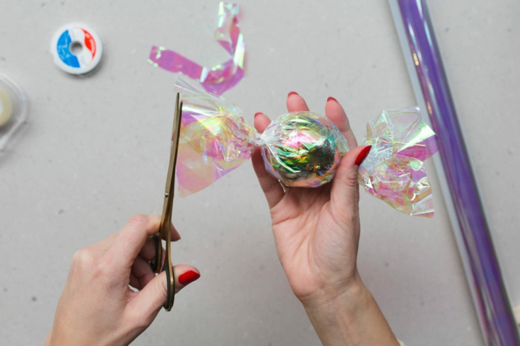 Decori natalizi, palla di Natale avvolta in cellophane, tagliare con le forbici