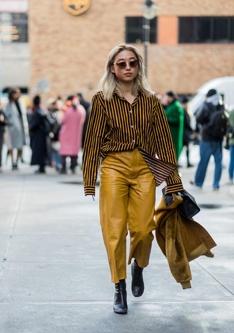 Ragazza che cammina, donna con capelli biondi, pantalone di pelle giallo