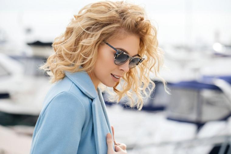 Capelli corti ondulati, colorazione capelli biondo, taglio caschetto ricci, donna con cappotto azzurro