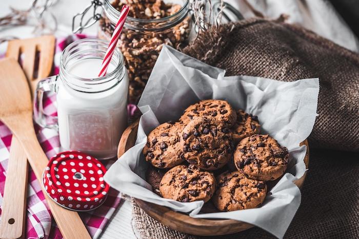 Ciotola di legno, piatto con cookies, biscotto al cioccolato, barattolo di vetro con latte