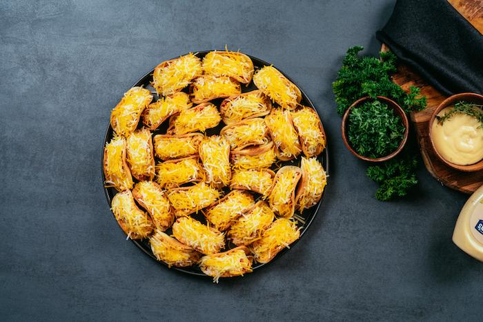 Teglia con mini tacos, tacos ricetta, formaggio cheddar grattugiato, prezzemolo tritato