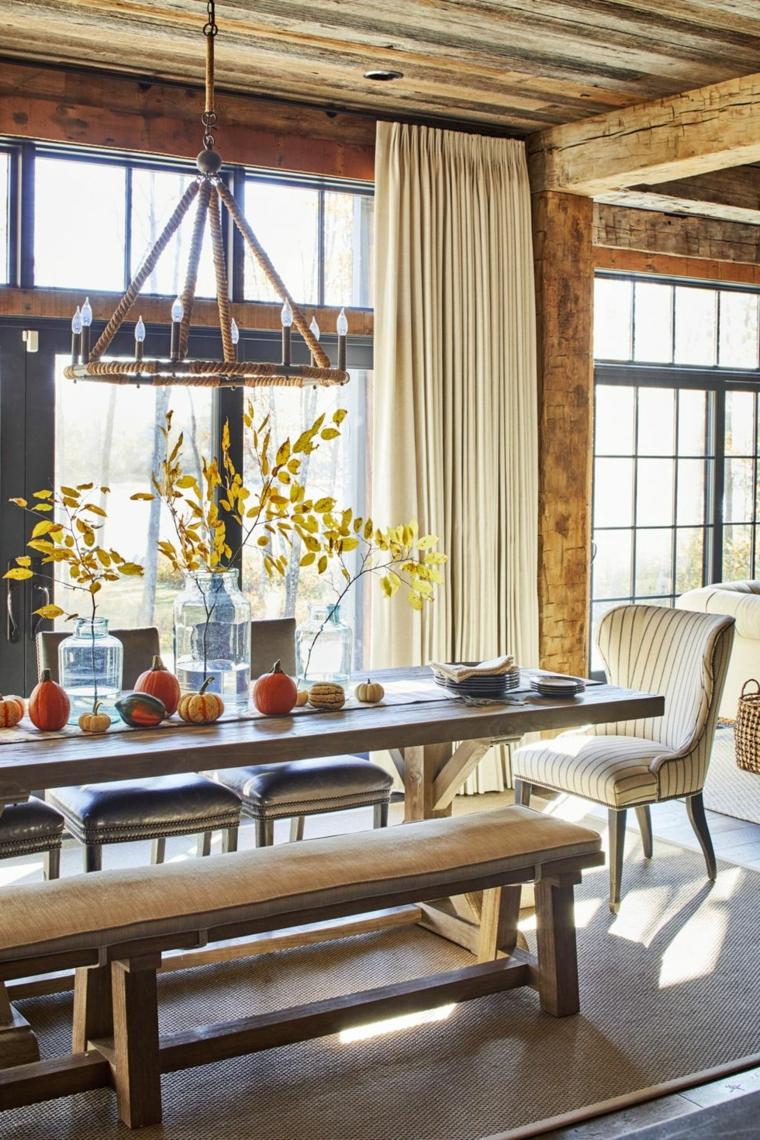 Sala da pranzo con tavolo di legno, centrotavola con vasi, rametti con foglie secche