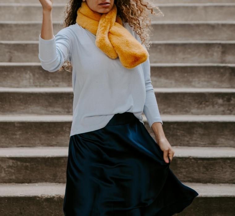 Sciarpa di colore giallo, donna che sta sulle scale, gonna e maglione autunnale