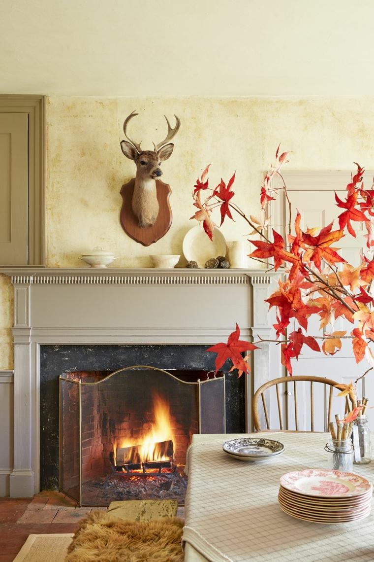 Vaso di vetro, rametti con foglie secche, soggiorno con camino, decorazioni autunno
