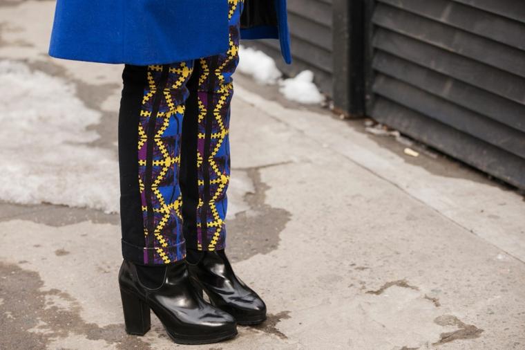 Stivaletti di pelle lucida, pantalone nero con ricami, cappotto lungo colore blu