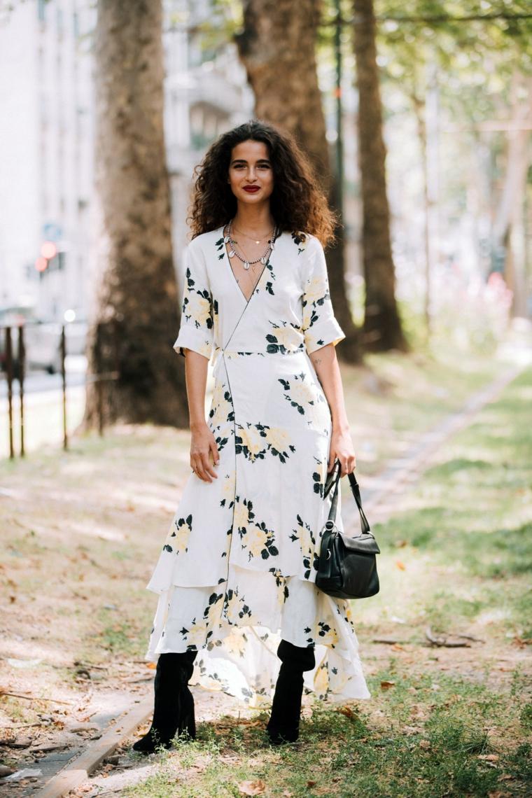 Donna con capelli ricci, maxi abito floreale, parco con alberi, stivali neri da donna
