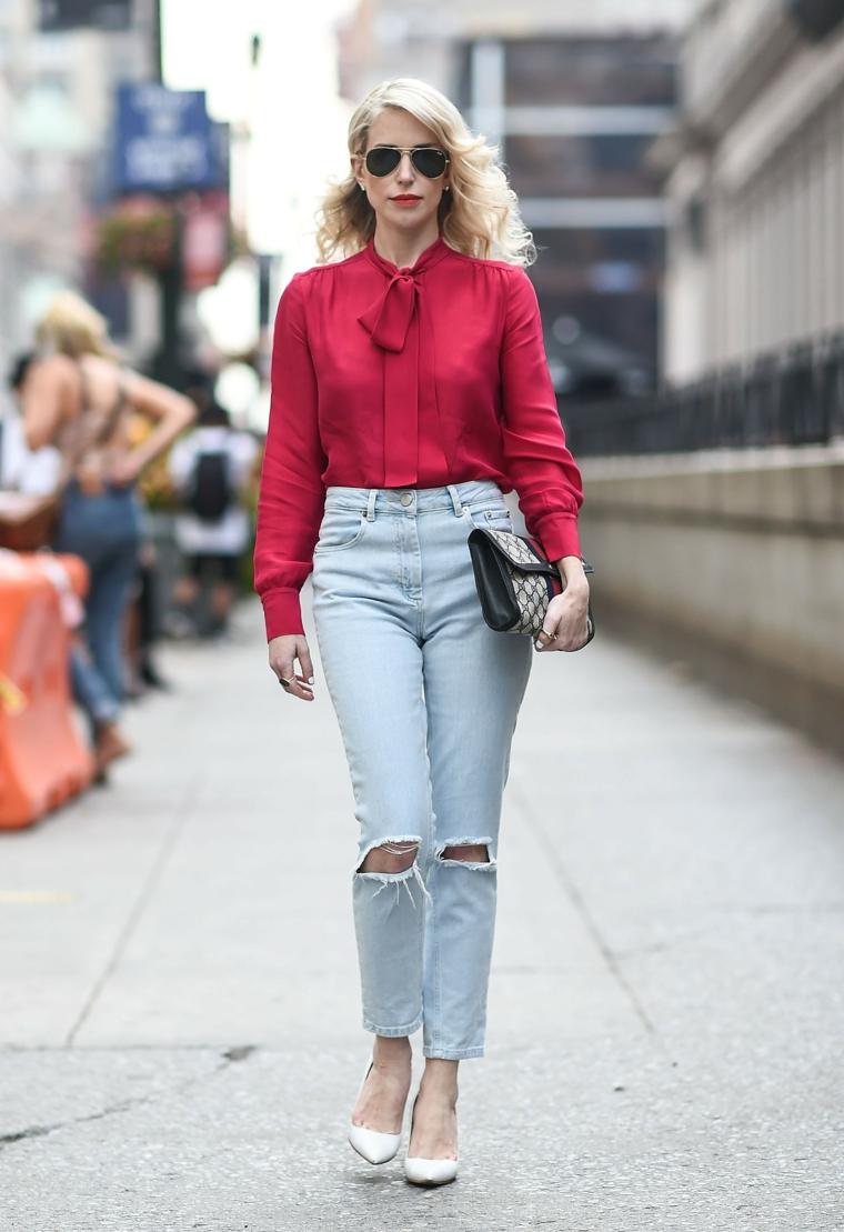 Donna che cammina, camicia rossa con nodo, jeans vita alta con strappi, borsetta clutch a mano
