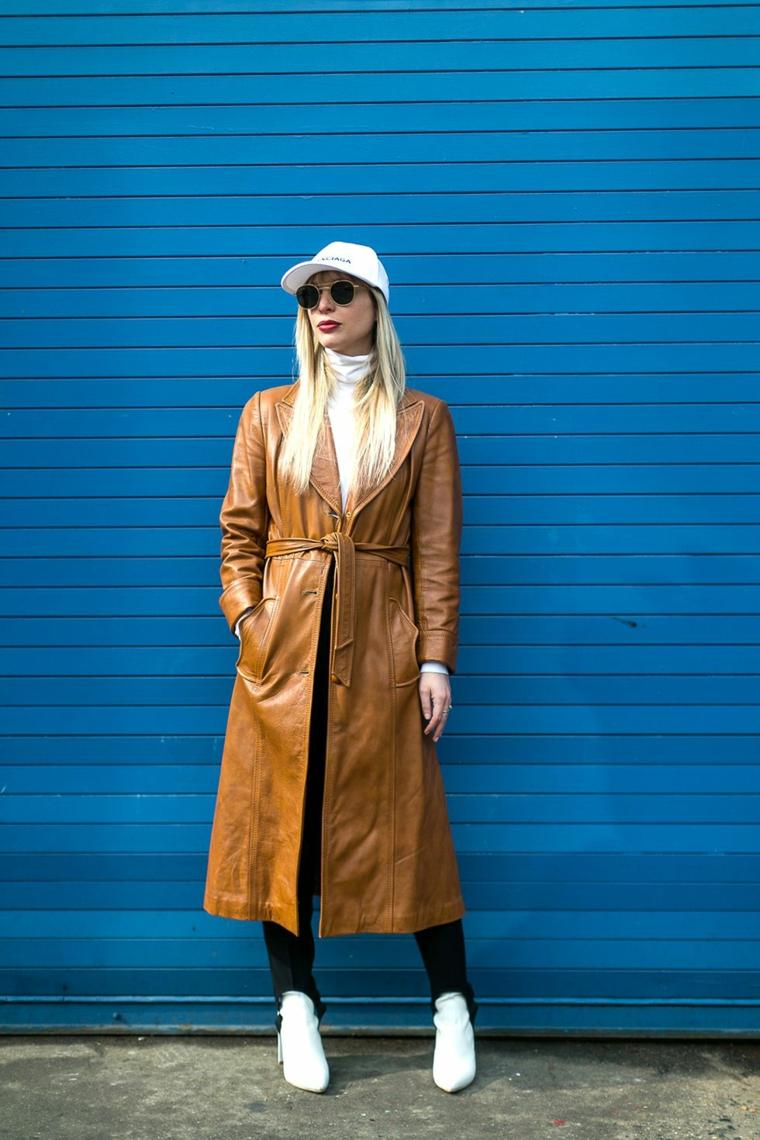 Donna con capelli biondi, cappotto in pelle marrone, stivaletti bianchi in pelle