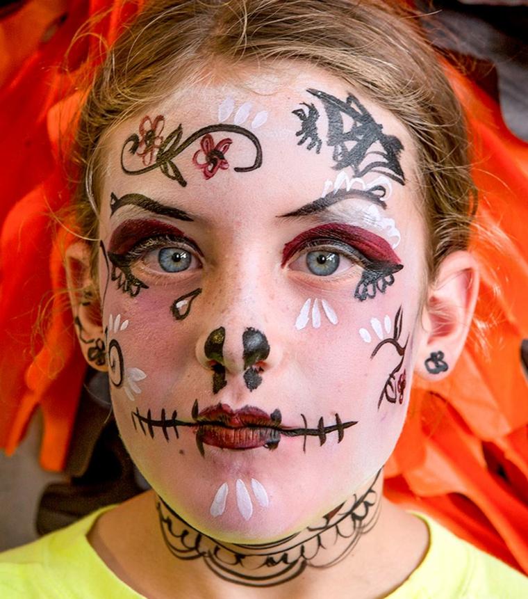 Bimba truccata come sugar skull, disegni fiori sul viso, travestimento per Halloween