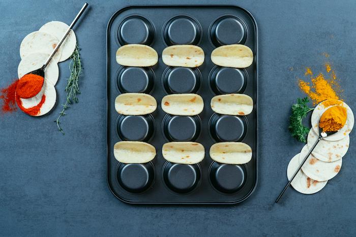 Teglia da muffin rovesciata, cucchiaio con pepe rosso, tortillas ripieno