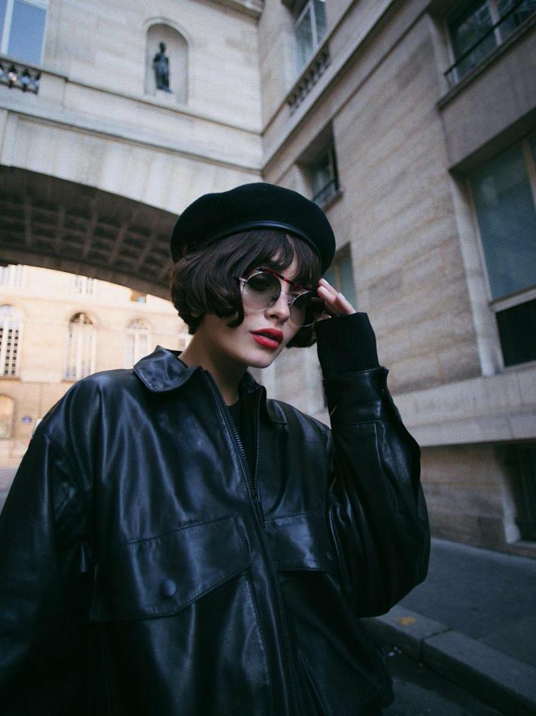 Taglio corto capelli ricci, ragazza con cappello, colorazione capelli neri, giacca di pelle nera