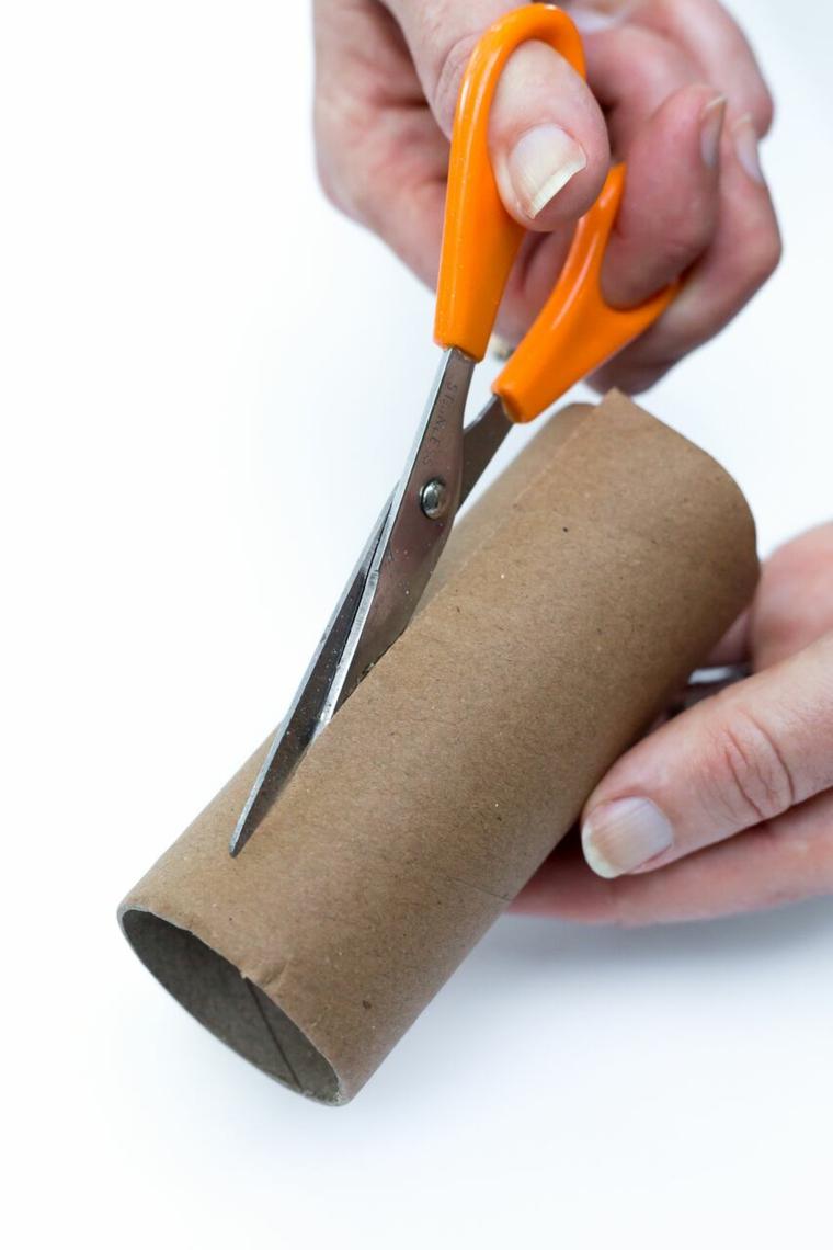 Tagliare con le forbici, rotolo di carta igienica, mani di una donna, tutorial segnaposto