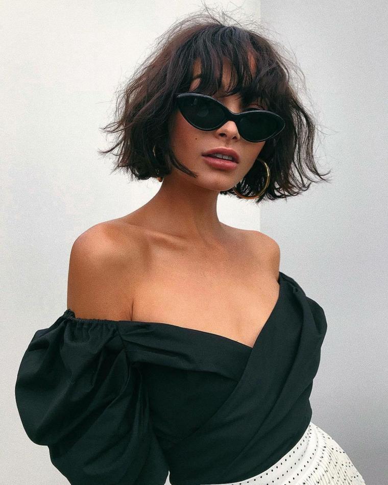 Acconciature capelli ricci, pettinatura con frangia, taglio pari corto, donna con occhiali da sole