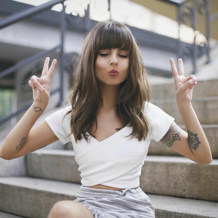 Tatuaggi sulle braccia, taglio capelli con frangia, Taglio capelli asimmetrico, ragazza seduta sulle scale