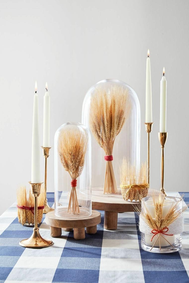 Centrotavola con vasi di vetro, mazzetti di grano, quattro candelabri, tovaglia bianco e blu