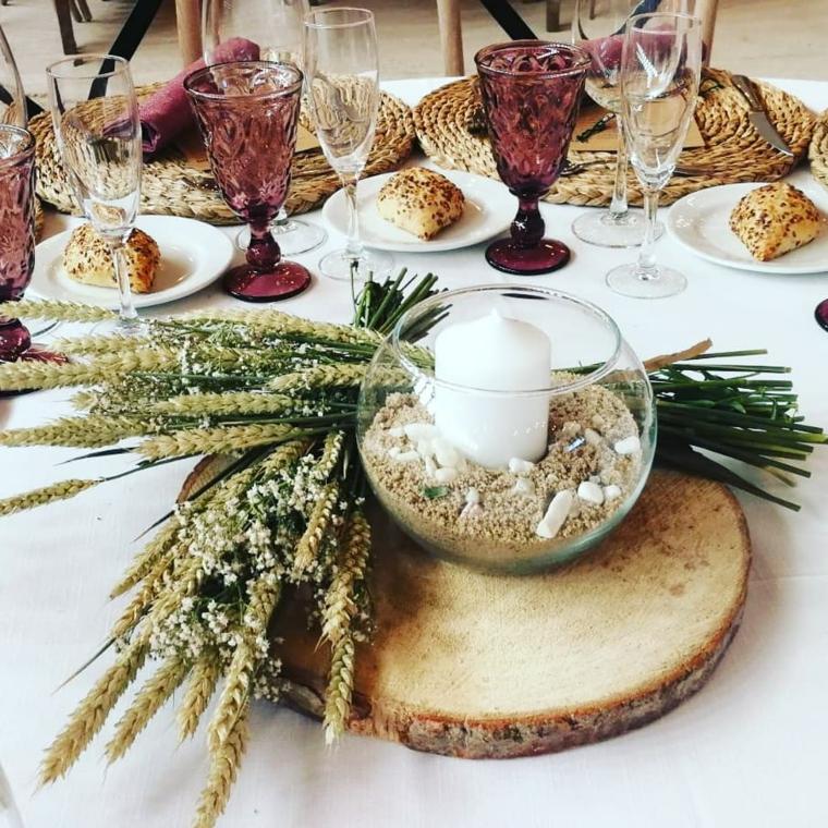 Tavola apparecchiata autunno, mazzetti di piantine, portacandele con sabbia, calici di vetro