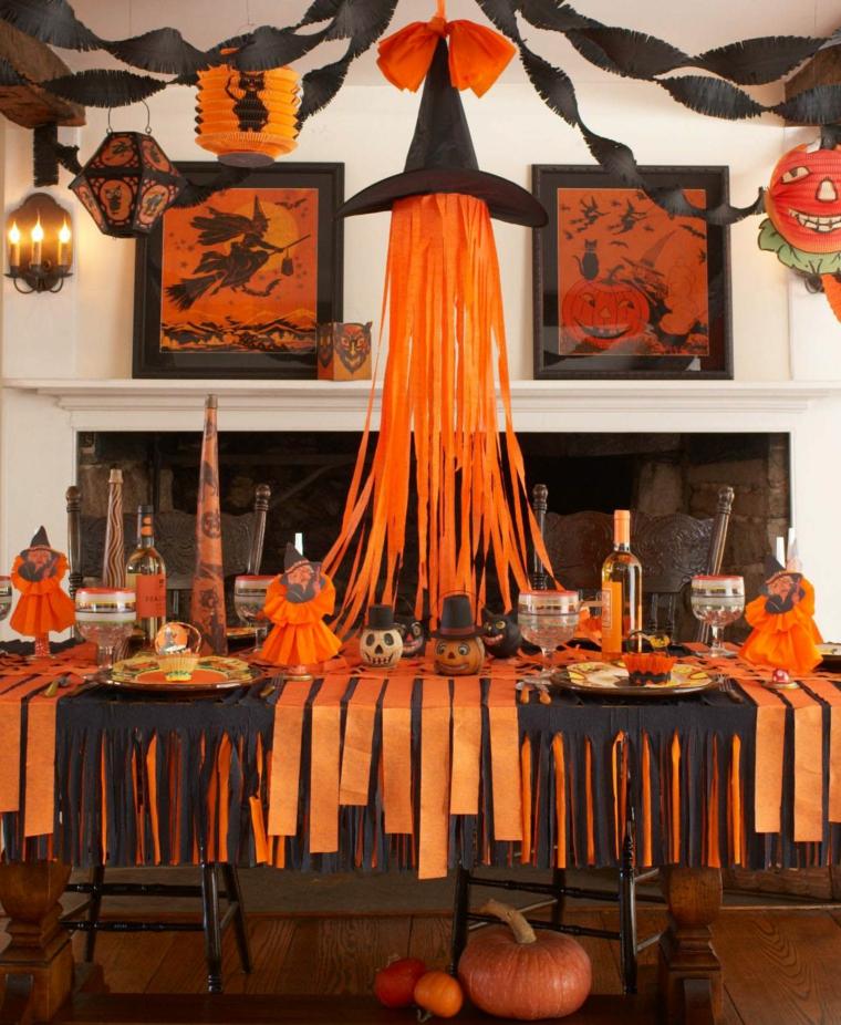 Tavolo con decorazioni, cappello strega di carta, ghirlanda per Halloween