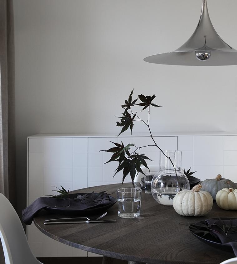 Centrotavola con zucche, vaso con ramo, tavola apparecchiata per Halloween