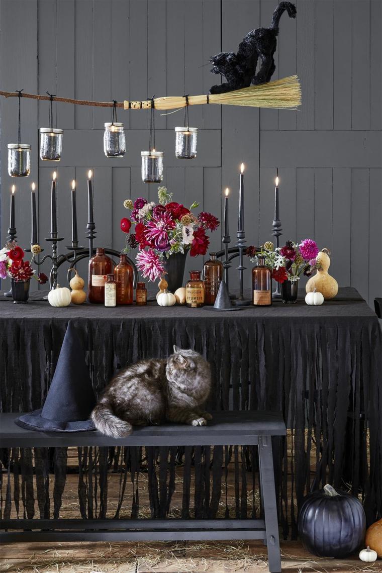 Tavolo apparecchiato per Halloween, lampada con scopa strega, lanterne con barattoli di vetro