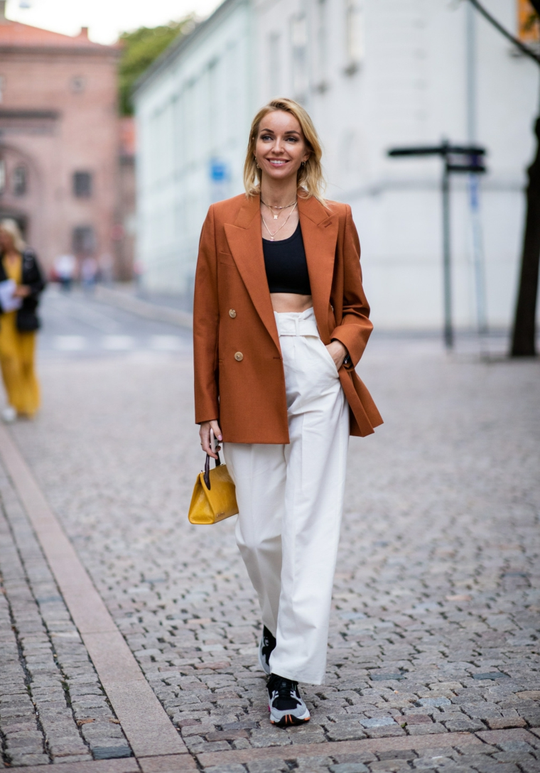 Pantalone donna vita alta, giacca colore marrone, donna che cammina, capelli biondi legati