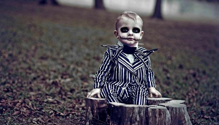 Trucchi Halloween facili, travestimento zombie, bimbo seduto su un tronco di legno