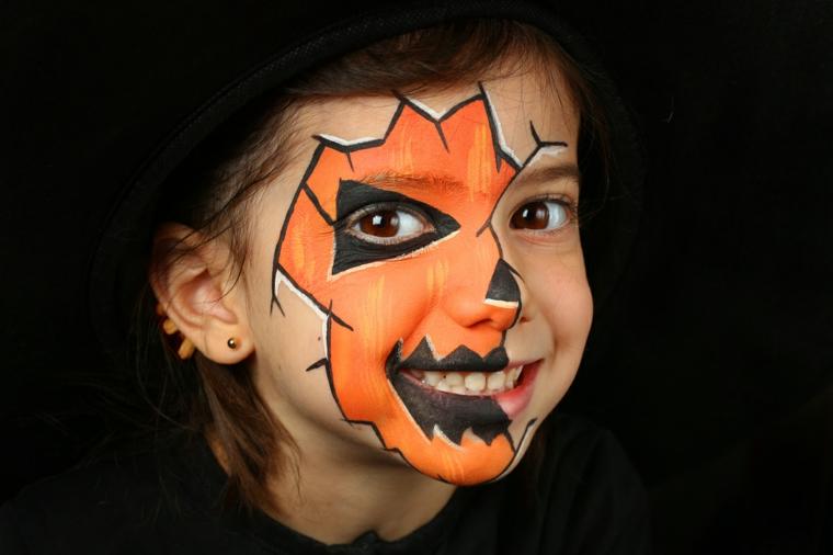 Trucco Halloween bambina, disegno sul viso, make up da zucca, bimba con sorriso