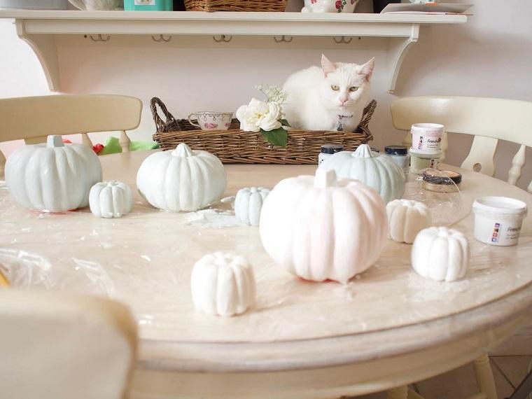Gatto in un cesto, tavolo con zucche dipinte, barattoli con vernice, addobbi di Halloween