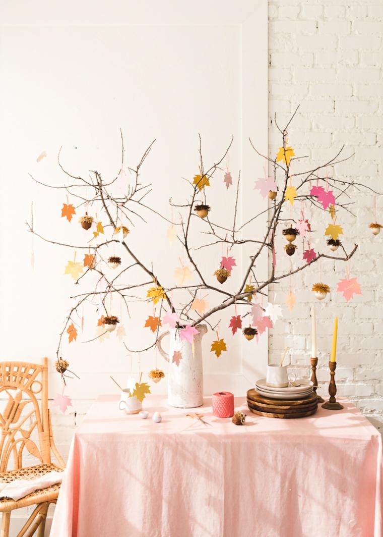 Vaso con rametti, rametti con foglie colorate, tavola con tovaglia rosa
