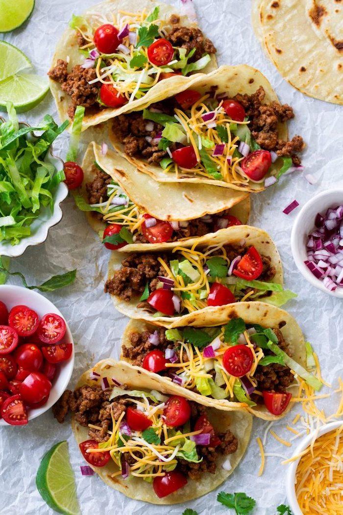 Piatti messicani, tacos con carne, ciotola con pomodorini, insalata romana tagliata