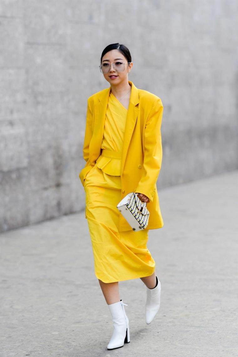 Donna con vestito giallo, cappotto stile maschile, stivaletti pelle bianca, donna che cammina