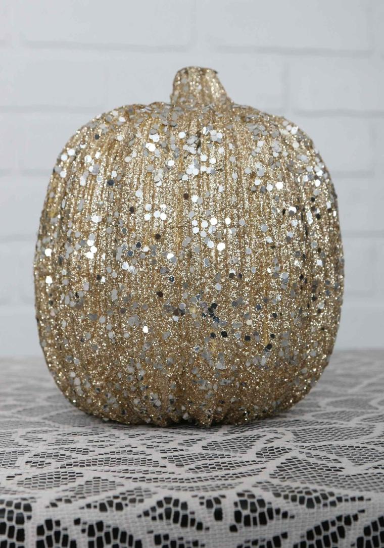 Zucca con lustrini, decorazioni per Halloween, tavolo con tovaglia a rete bianca